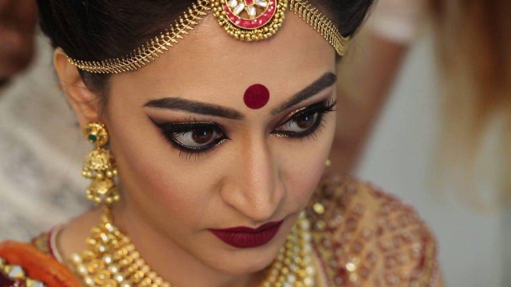 женщины Индии ходят с красной точкой на лбу